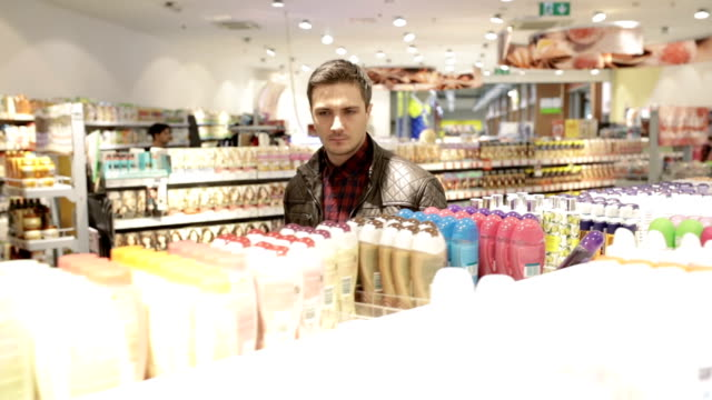 Young man shopping hygiene products, panning shot video