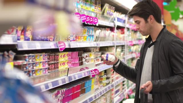 dolly: young man shopping in a supermarket - замороженные продукты стоковые видео и кадры b-roll