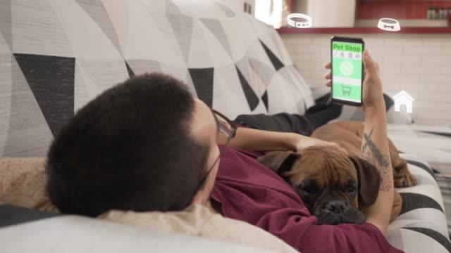 stockvideo's en b-roll-footage met jonge mens die in een online huisdierenopslag winkelt, die op de laag met zijn hond ligt - discountwinkel