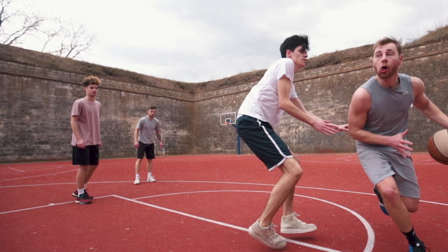 Young man showing his basketball skills Group of young adults playing amateur basketball outdoor practice drill stock videos & royalty-free footage