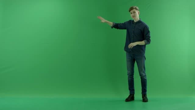 若い男が右側にある緑色の画面で天気予報を表示 ビデオ