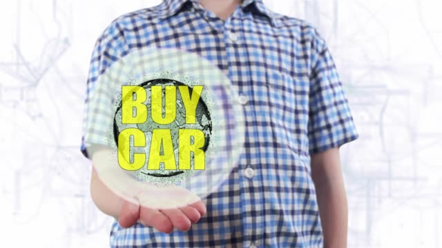 Young man shows a hologram of the planet Earth and text Buy car video
