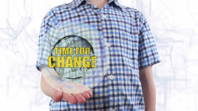 Young man shows a hologram of the planet Earth and text Time for change