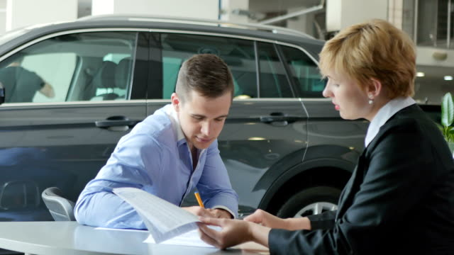 A young man signing papers at an automobile store A man and a woman are sitting at a table in an automobile store. A man is sitting on the background of a dark car. A handsome man signs papers. The storekeeper shows the man a place for a signature. People talks and smile a little. car rental stock videos & royalty-free footage