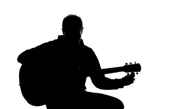 Young man silhouette tuning up guitar, professional writing song, musical hobby video