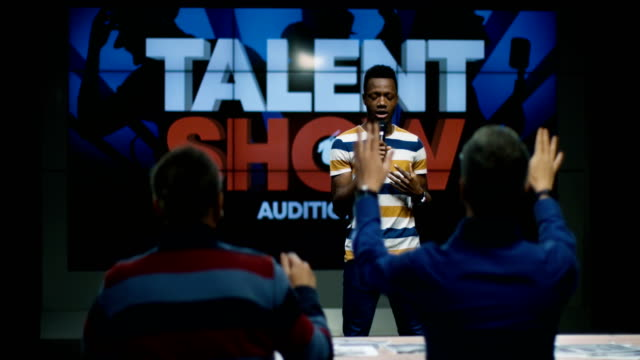 Young man singing at talent show Medium long shot of young man's singing in front of jury contest stock videos & royalty-free footage