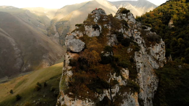 A young man sits in a lotus position on top of a rock in the mountains and meditates Aerial view