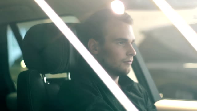 stockvideo's en b-roll-footage met jonge man zit achter het stuur van een dure auto - parkeren