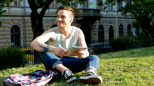 Young man sitting in park with digital tablet and using wi-fi internet video