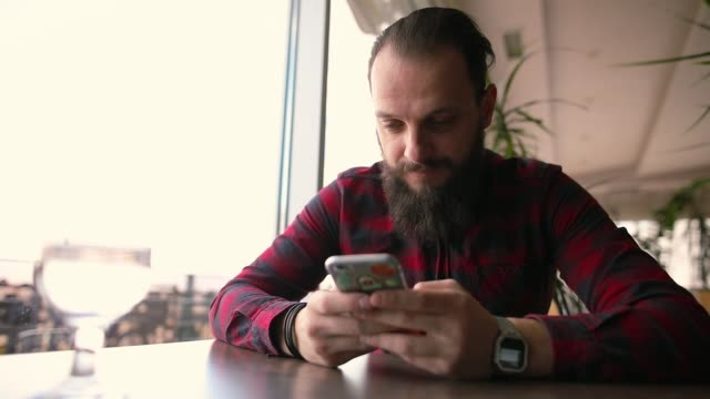 young man sitting in rooftop coffee shop near window, using phone, sending text messages - solo un uomo giovane video stock e b–roll