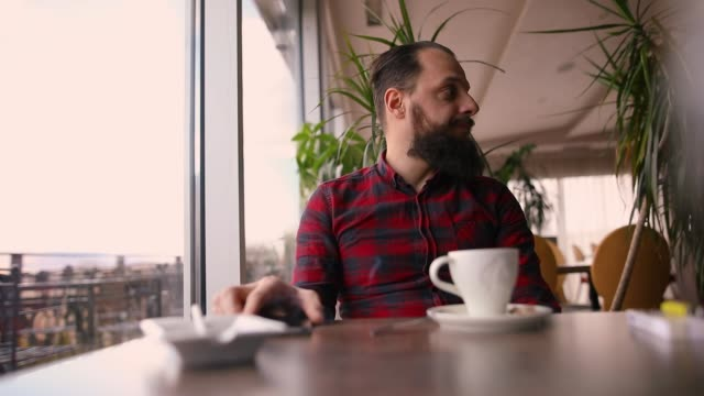 Young man sitting in rooftop coffee shop near window Young man sitting in rooftop coffee shop near window plaid stock videos & royalty-free footage