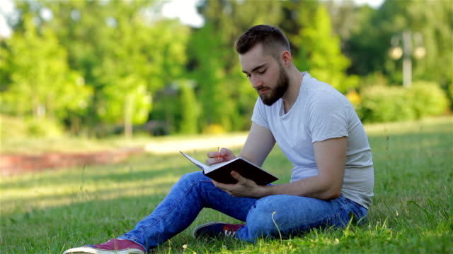 Young man sitting in the park with his diary video