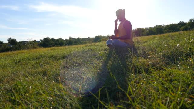 ung man sitter i yoga posituren på gröna gräset på ängen och mediterar. muskulös kille avkopplande i lotus pose på naturen. rekreation utomhus på solig dag. vackert landskap i bakgrunden. närbild - korslagda ben bildbanksvideor och videomaterial från bakom kulisserna
