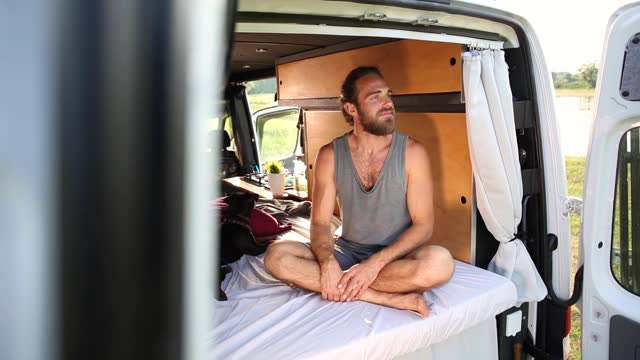 Young man sitting inside his camper van