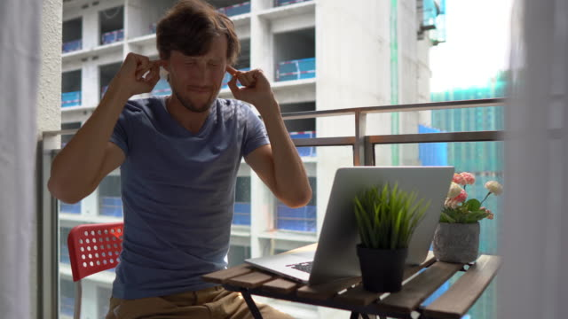 young man sitting on a balcony with a notebook and suffering from a loud noise produced by a construction site nearby. concept of noise pollution in big cities - coprire video stock e b–roll