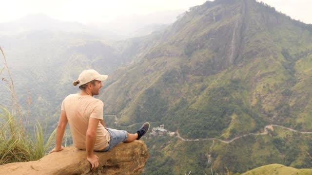 stockvideo's en b-roll-footage met jonge mens die op rots bovenop mooie bergwaaier in sri lanka zit die het groene weelderige landschap van dit tropische klimaat na het wandelen bewondert en tot de bovenkant bereikt - camelia white