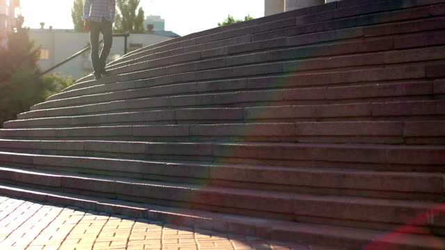 Young man sitting on stairs, problem, depression, square daytime video