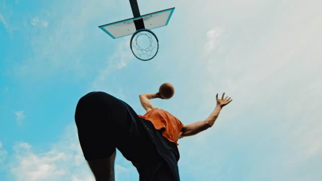 vidéos et rushes de ms super slow motion jeune homme slam dunking basket-ball - inclinaison vers le haut