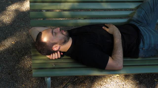 Young man sleep on a bench
