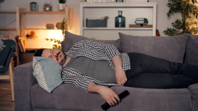 vídeos de stock e filmes b-roll de young man sleeping on couch at home holding remote control for television - sofá
