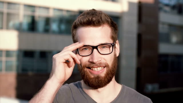 Young man smiling and looking at camera. Portrait of happy handsome young guy in urban street. Male touches the glasses video