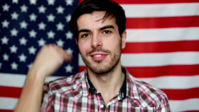 Young man smiling in front of American flag video