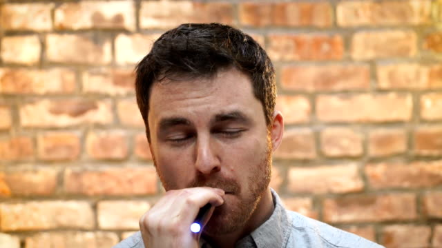genç bir adam kapalı bir e sigara içiyor - nikotin stok videoları ve detay görüntü çekimi