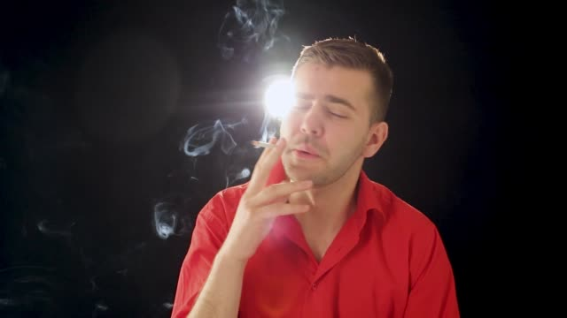 Young man smokes cigarette in studio, addiction problem, black background, close up