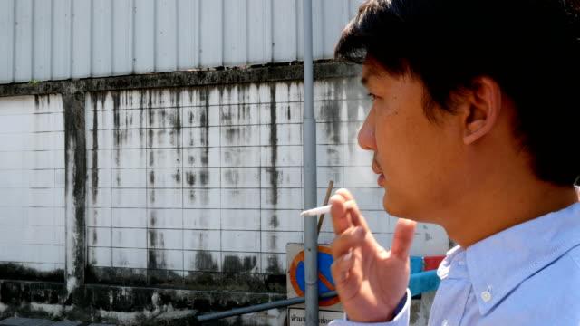 若い男が街でタバコを吸って - 人の居住地点の映像素材/bロール