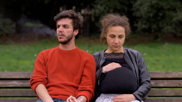 parkta hamile genç kadının yanında oturan sigara içen genç adam - nikotin stok videoları ve detay görüntü çekimi