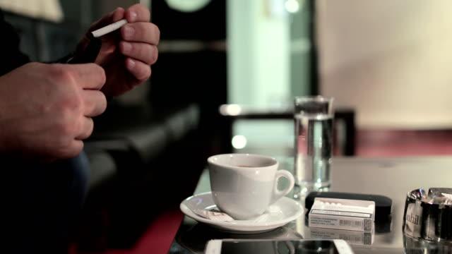 giovane fuma e sigaretta e beve caffè - nicotina video stock e b–roll