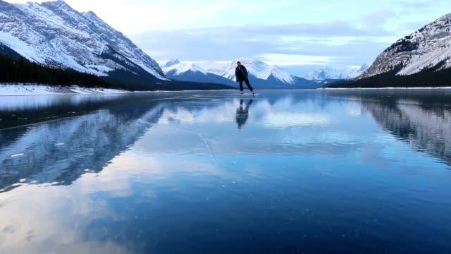 young man solo skates on beautiful mountain lake - łyżwa filmów i materiałów b-roll