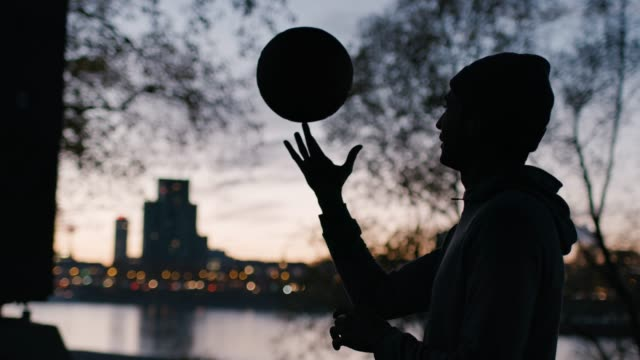 Young man spinning basketball on finger in city