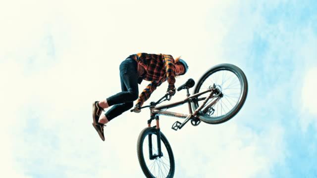 ms-junge mann spinnen mit bmx fahrrad gegen bewölktem himmel - stunt stock-videos und b-roll-filmmaterial