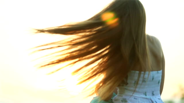 Young man spins and holds happy woman in arms twirling together at sunset backlit close up. Boyfriend rotates carrying smiling long hair girlfriend in sunny evening summer meadow. Love togetherness video