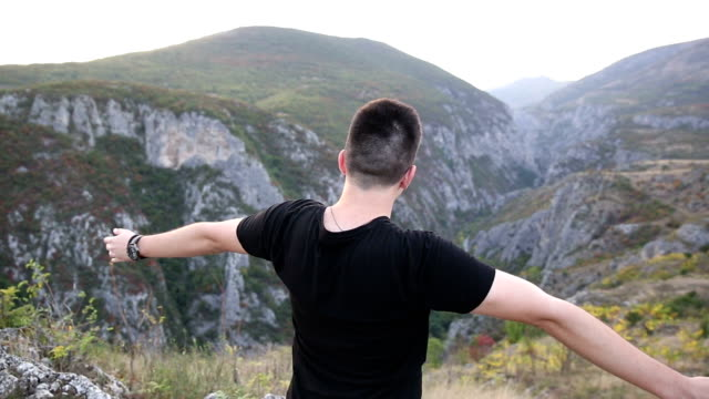 Young man spreads his hands on the mountain