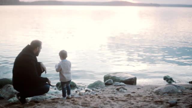Hombre joven en cuclillas en una orilla y hablar con el niño, de pie. Padre e hijo pasar tiempo juntos - vídeo