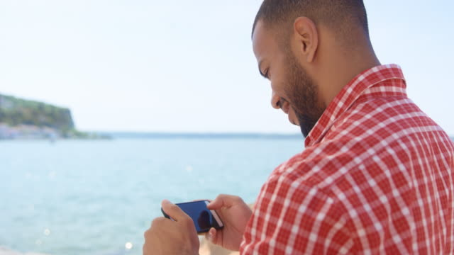 Young man standing by the sea and smiling while checking the photos he made with his smartphone