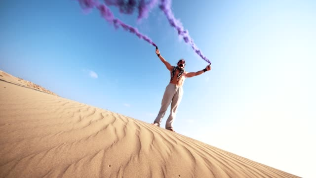 Young man standing in desert with smoke bombs video