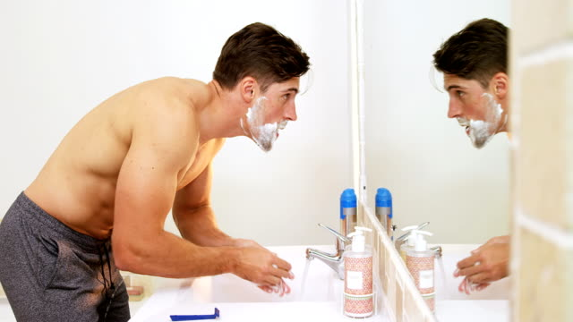 Young man standing in front of mirror washing his face with water 4K 4k video
