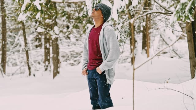 Young man standing in the woodlands and enjoying the snowfall video