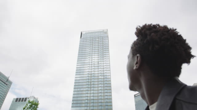 young man standing next to skyscraper. - international architecture stock videos & royalty-free footage