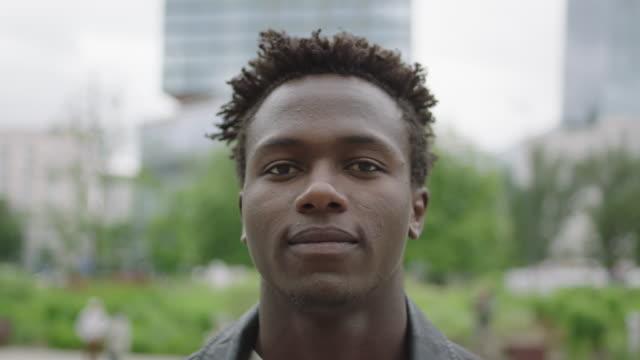 young man standing next to skyscraper.. - młodzi mężczyźni filmów i materiałów b-roll