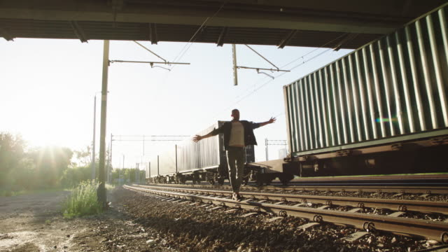 Young man standing on the railroad truck. Rock and roll style. video