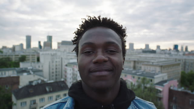 Young man standing on the roof. Looking at camera Portrait of African man standing on roof. Cityscape in the background black people stock videos & royalty-free footage