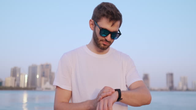 A young man standing on the waterfront in the summer uses the smart watch screen