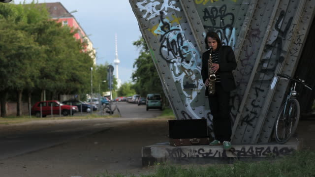 young man stands alone under bridge and play saxophone video