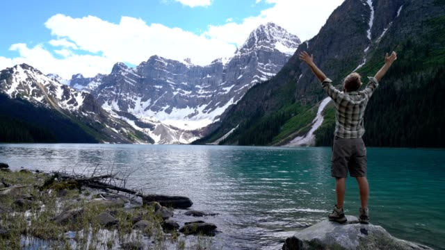 Young man stands by the lake arms wide open to embrace nature video