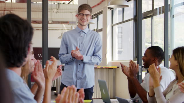 Young man stands clapping with seated colleagues at meeting video