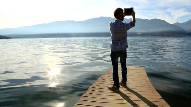 Young man stands on jetty above lake, uses digital tablet video